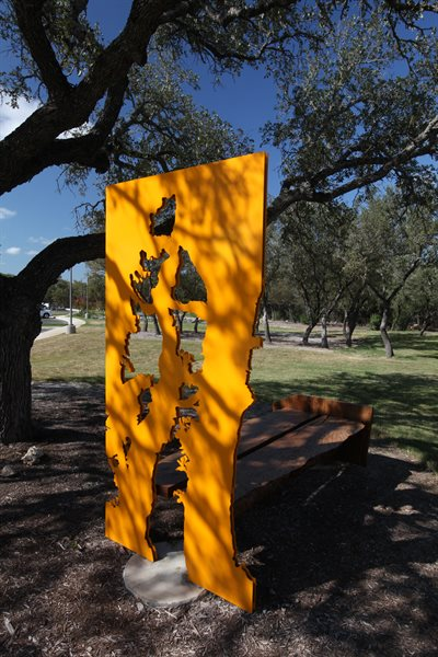The metal cutouts of the bench mimic the trees that the wood was taken from.