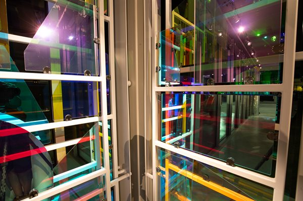 The vertical corners and horizontal suspended sections of glass are analogous to opened theatrical curtains.
