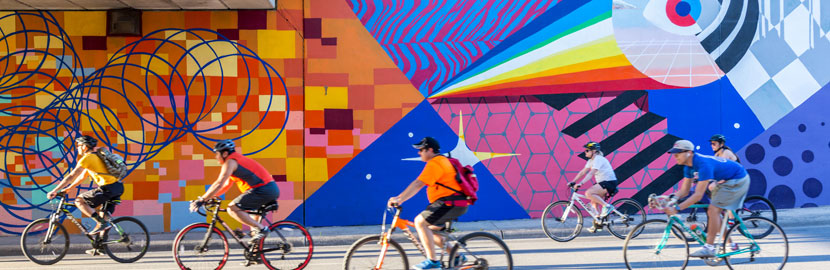 Cyclists in front of art mural